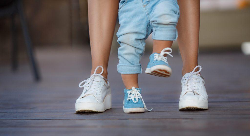 mom helping baby take baby steps